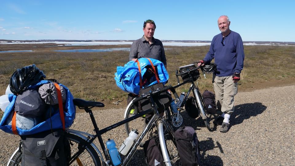 Deux hommes et leurs vélos sur une route de gravier devant la toundra où se trouvent de petits lacs et des résidus de neige.