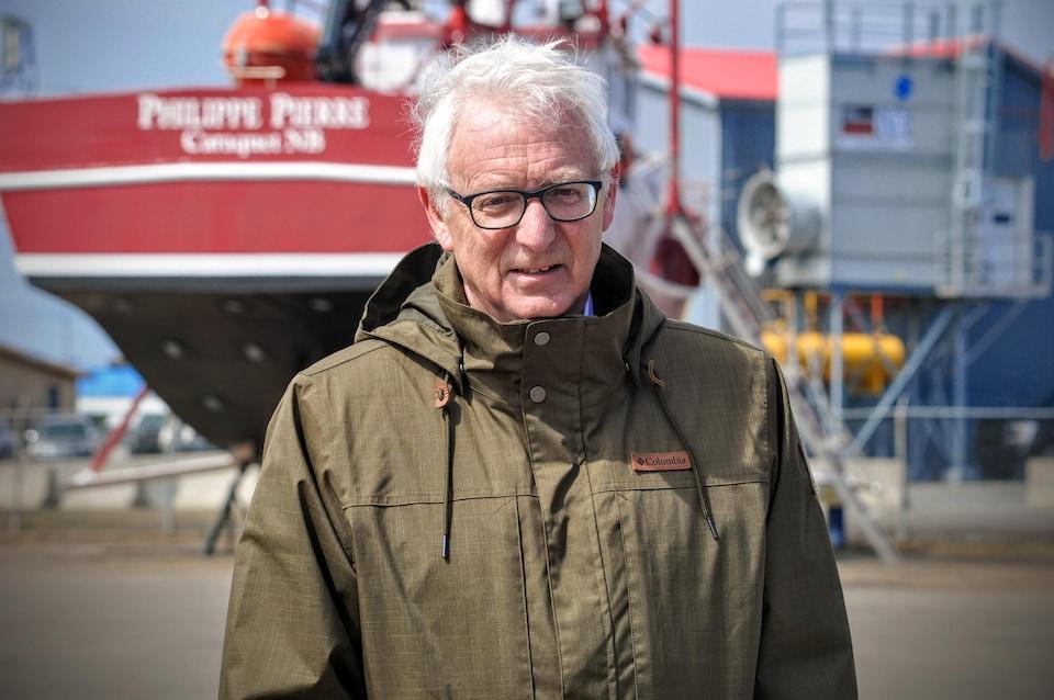 Jean Lanteigne, debout devant un gros bateau de pêche.