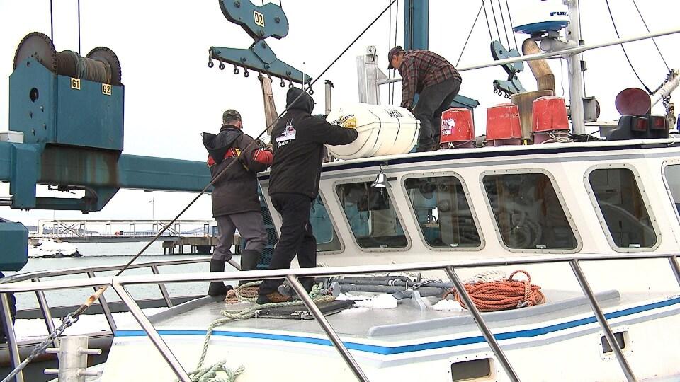 Des hommes embarquent une bouée sur un bateau.