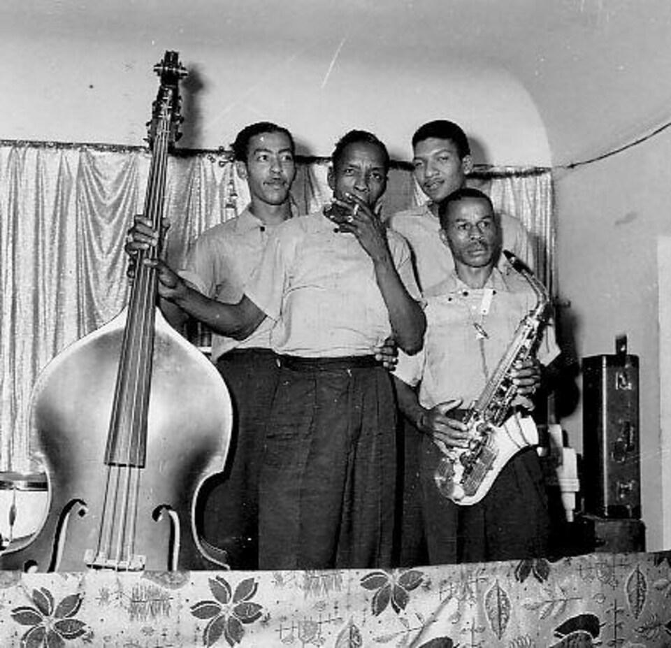 À droite, Robert «Pee Wee» Carter tenant son saxophone, accompagné de ses musiciens