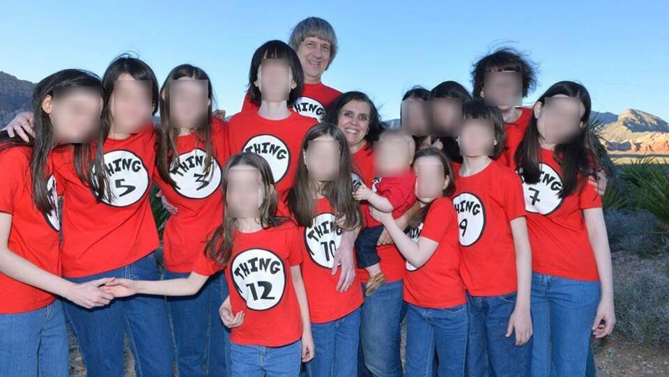 La famille Turpin pose toute souriante tandis que tous sont vêtus d'un chandail rouge sur lequel est inscrit leur âge.