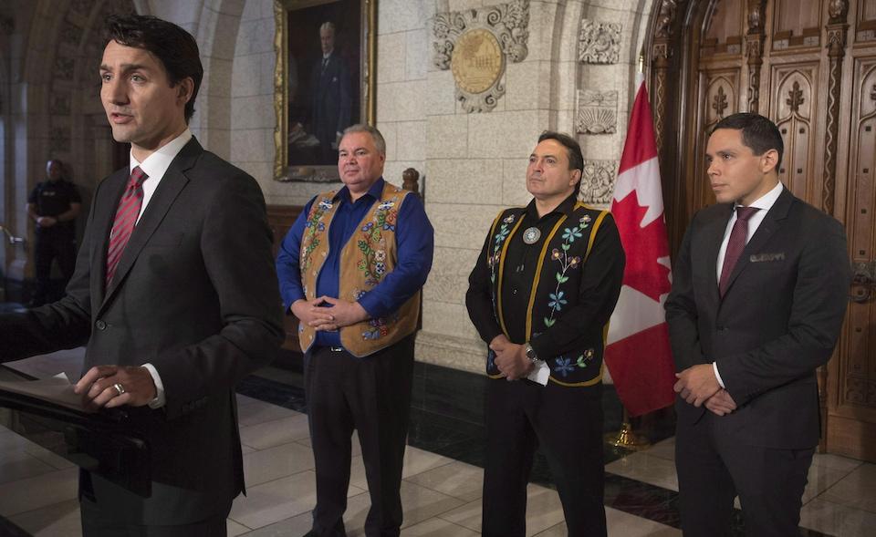 Les deux hommes se tiennent debout devant le drapeau du Canada.