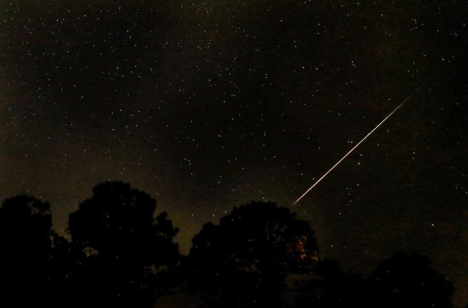 Le ciel est sombre et il y a une ligne de lumière qui le traverse, c'est une étoile filante.