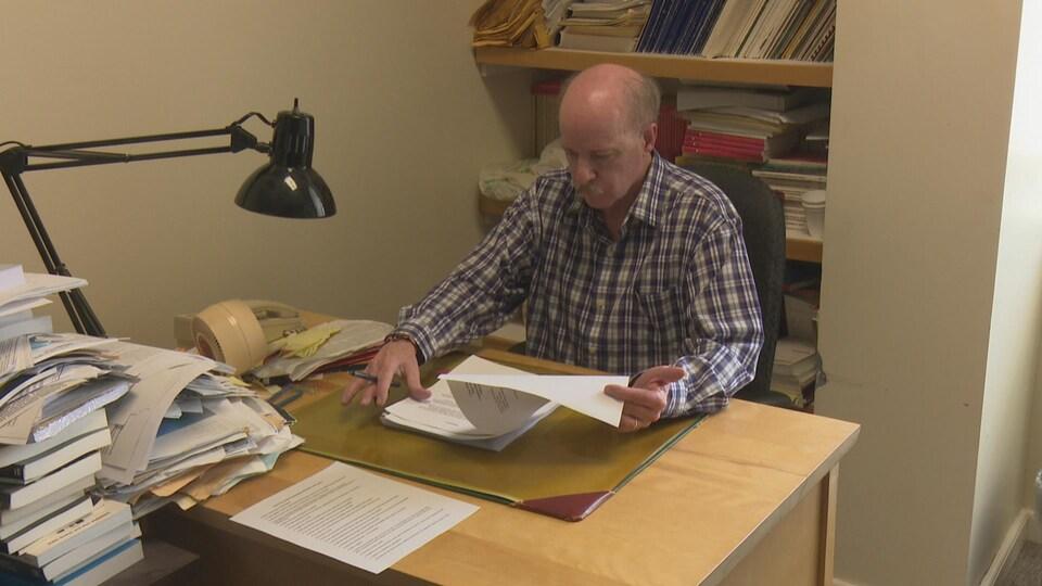 peter McKenna est assis à son bureau. Il lit des documents.