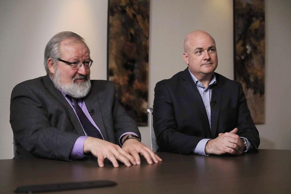 Deux hommes assis à une table répondent à des questions.