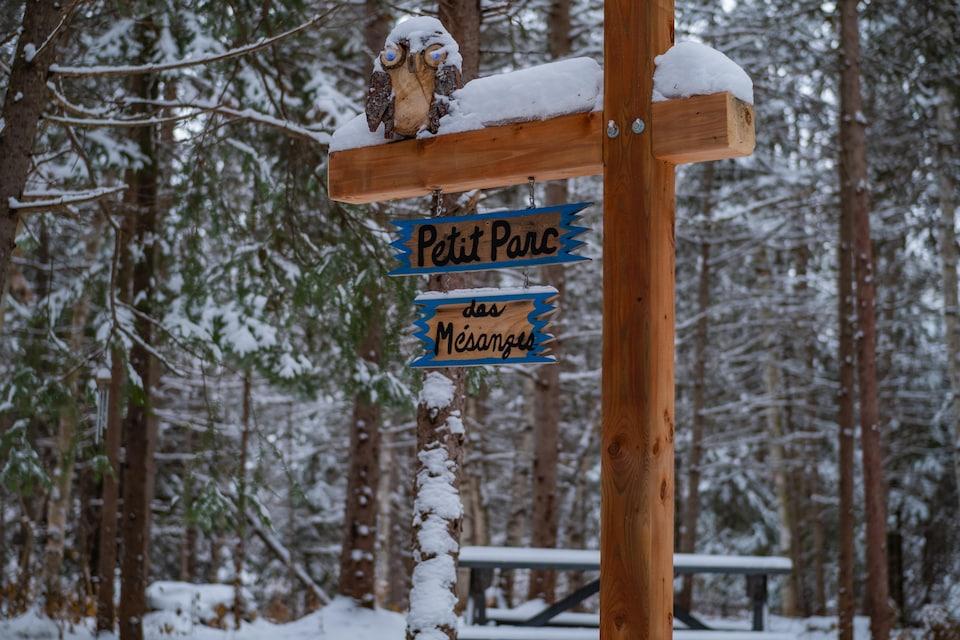 Une affiche en bois indique Petit Parc des Mésanges, devant une aire de repos dans un sentier pédestre.