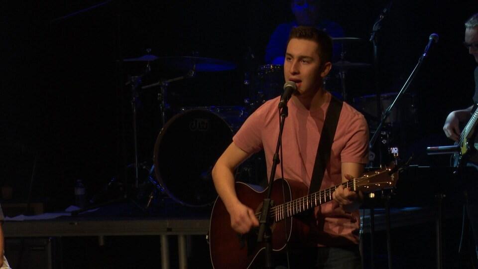 Un jeune homme au micro, guitare à la main