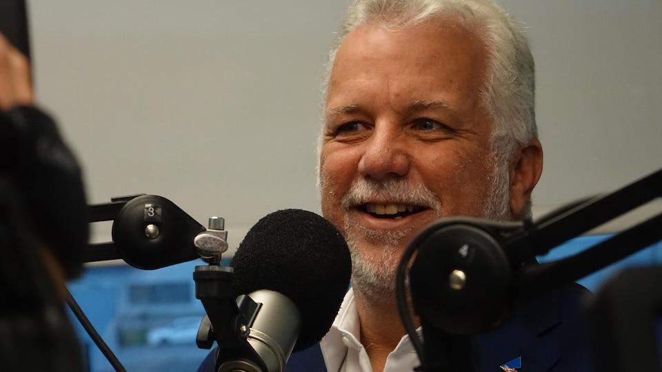 Philippe Couillard affiche un sourire dans un studio de radio.
