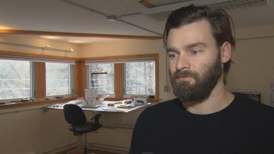 Jean-Philippe Brousseau répond aux questions d'une journaliste dans son atelier.