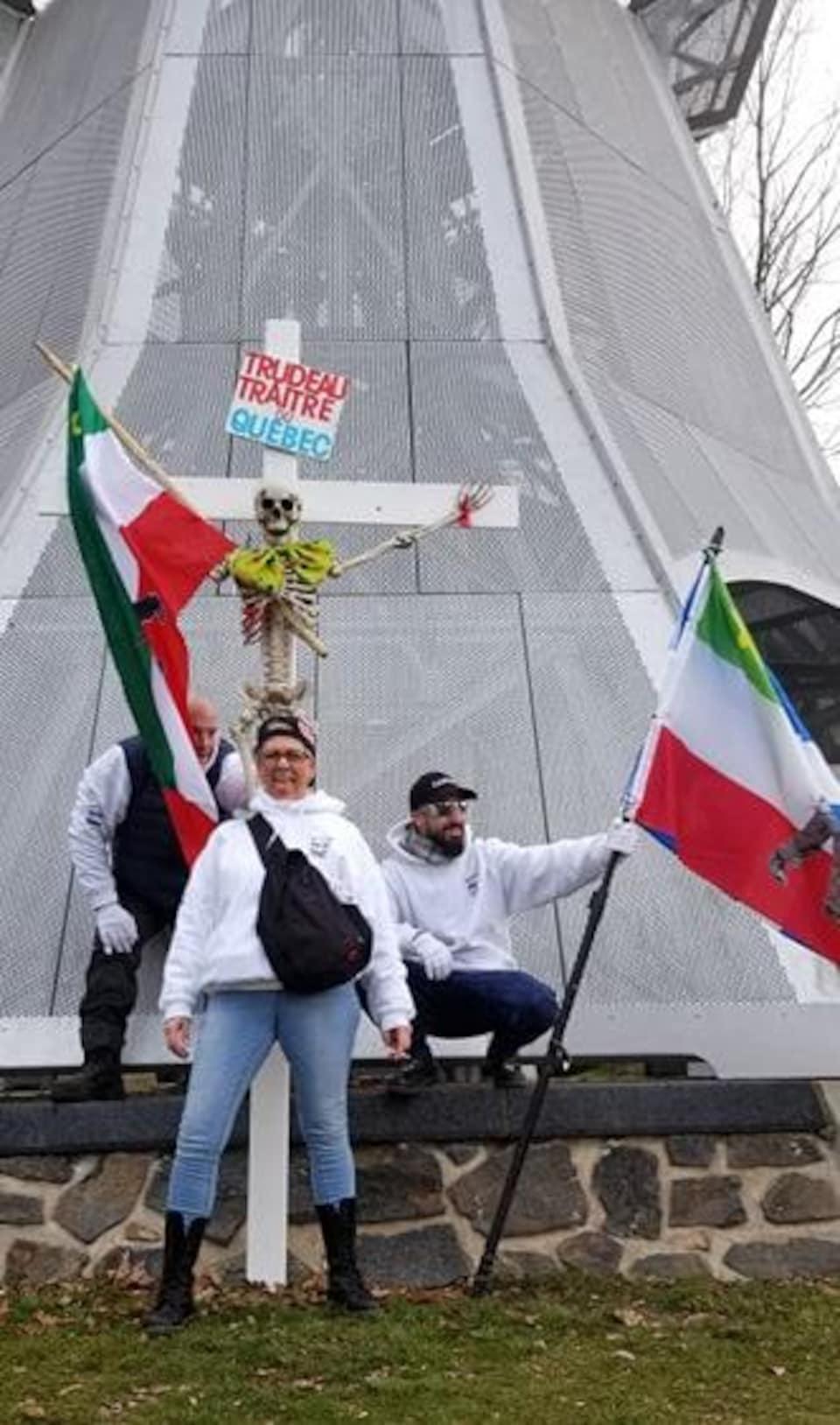 On voit trois manifestants portant les drapeaux du Québec et des Patriotes, ainsi qu'une croix avec un squelette et une pancarte qui dit « Trudeau traître du Québec ».