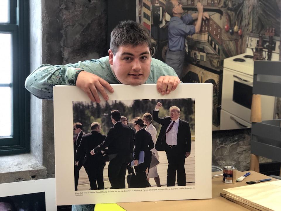 Un jeune homme tient une photo du Sommet du G7 dans ses mains.