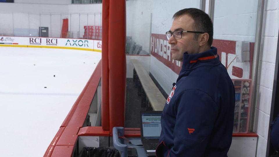 On voit M. Allard, de profil, près du banc des joueurs. Il surveille les joueurs pendant leur entraînement. Devant lui, un ordinateur portable affiche des données.