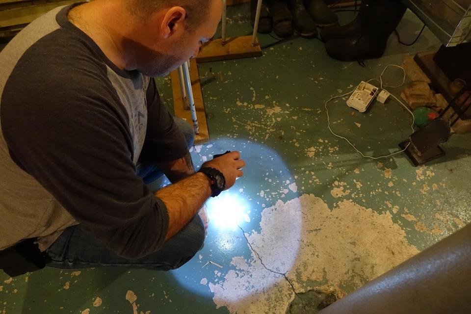 Pierre Fontaine pointe avec la lampe de son téléphone une fissure sur le plancher de son sous-sol qui se serait agrandie à la suite des dynamitages.