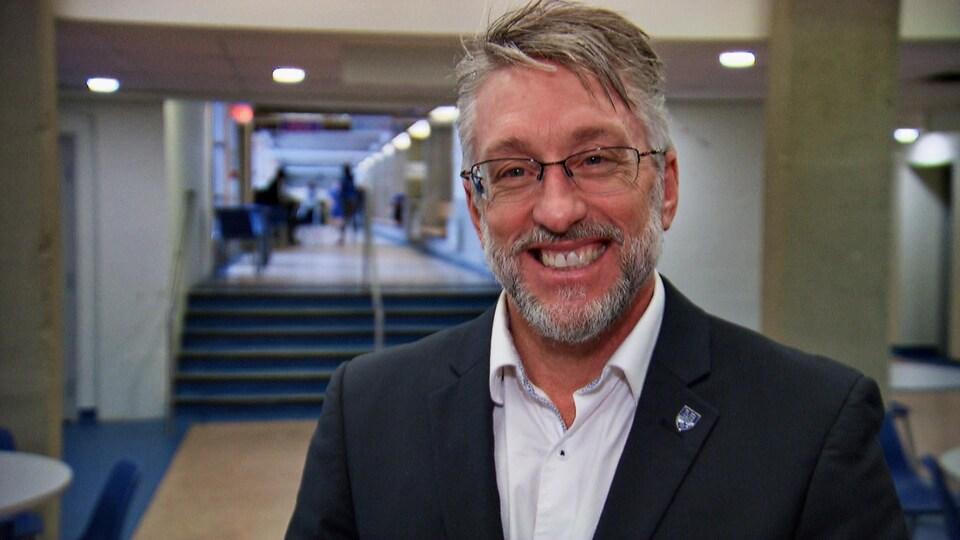 Un homme souriant dans un corridor d'école.