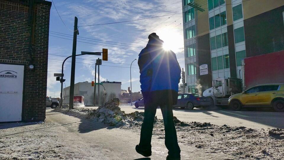 Un piéton marche dans le froid dans une rue de Winnipeg.