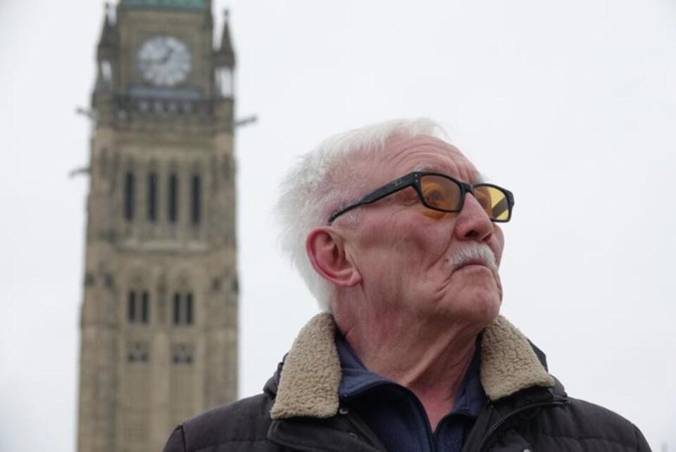Un homme devant la Tour de la Paix sur la Colline du Parlement à Ottawa.