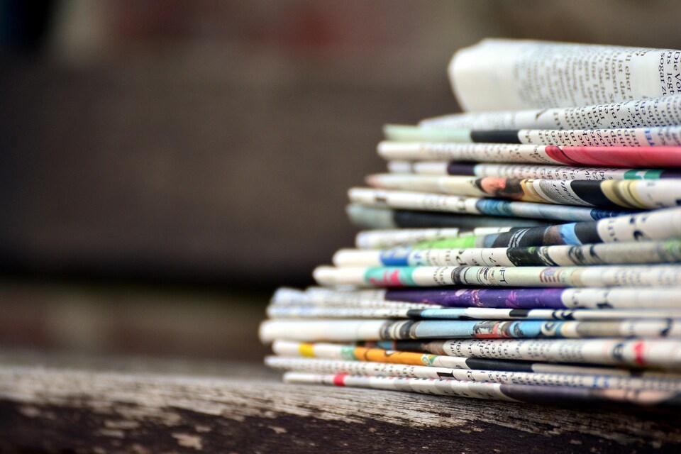 Une vingtaine de journaux pliés posés sur une table.