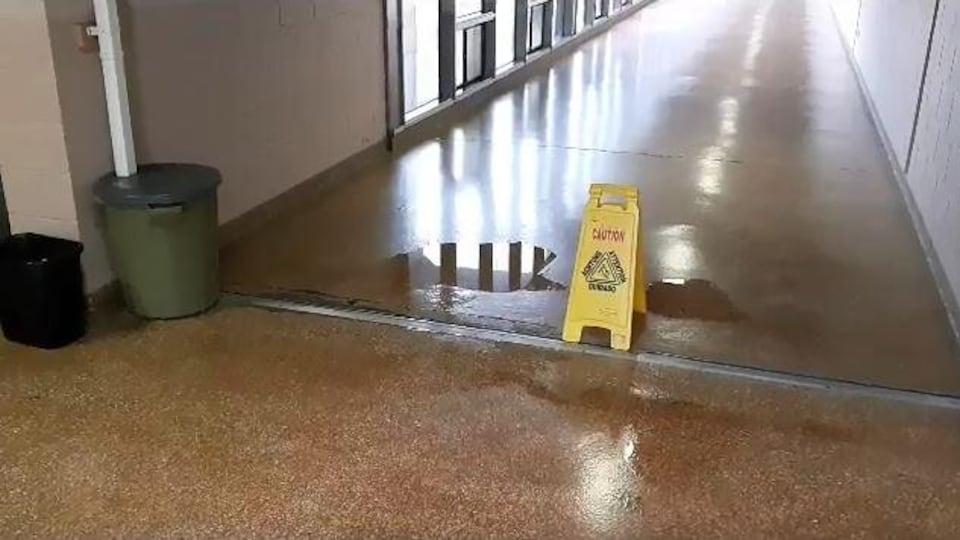 Une flaque d'eau dans un corridor et une affiche indiquant que le plancher est glissant.