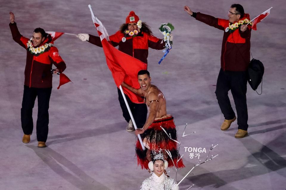 Torse nu, Pita Taufatofua brandit le drapeau de Tonga