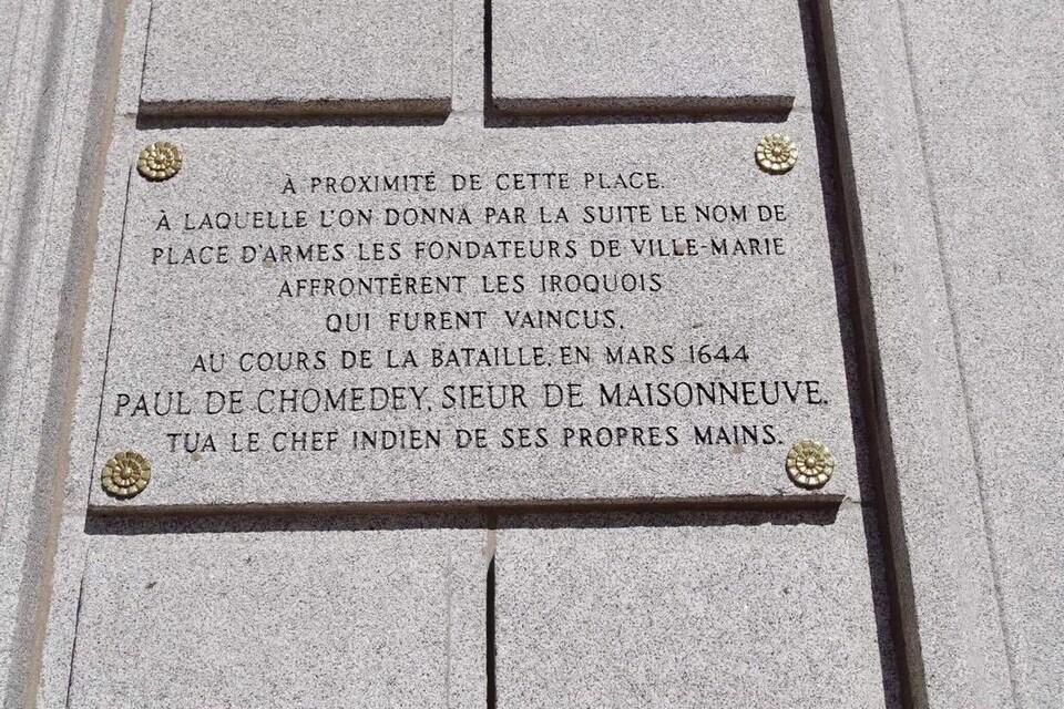 On peut lire : «À proximité de cette place à laquelle l'on donna par la suite le nom de place d'Armes, les fondateurs de Ville-Marie affrontèrent les Iroquois qui furent vaincus. Au cours de la bataille en 1644,  Paul de Chomedey, sieur de Maisonneuve tua le chef indien de ses propres mains.»