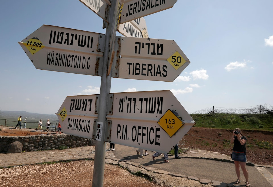 Une touriste prend en photo un panneau de signalisation installé sur le plateau du Golan.