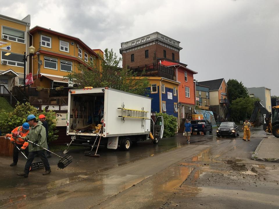 Des travailleurs nettoient l'eau et la boue au centre-ville de Gaspé