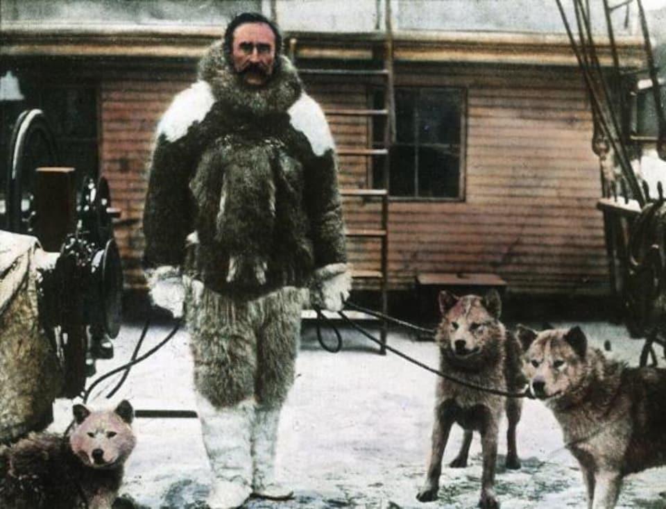 Un homme dans un habit polaire accompagné de ses chiens.