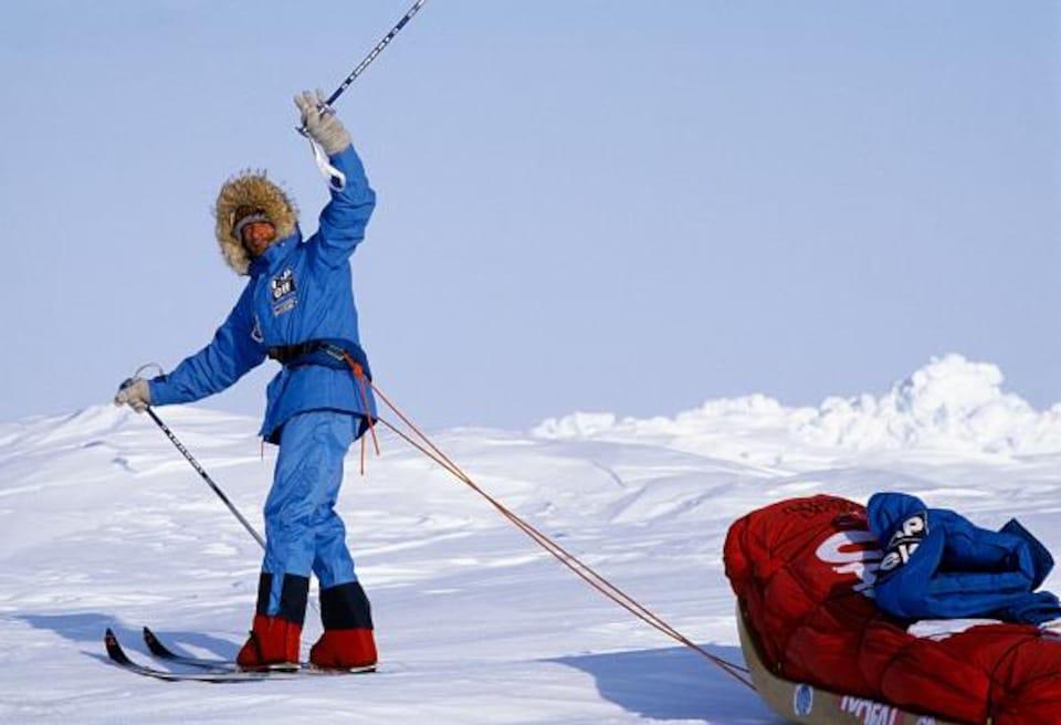Un homme à ski sur la glace tire un traîneau.