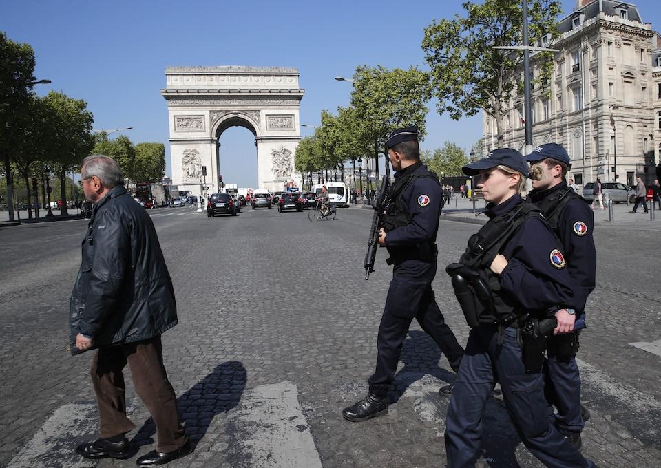 Trois policiers français armés traversent les Champs-Élysées.