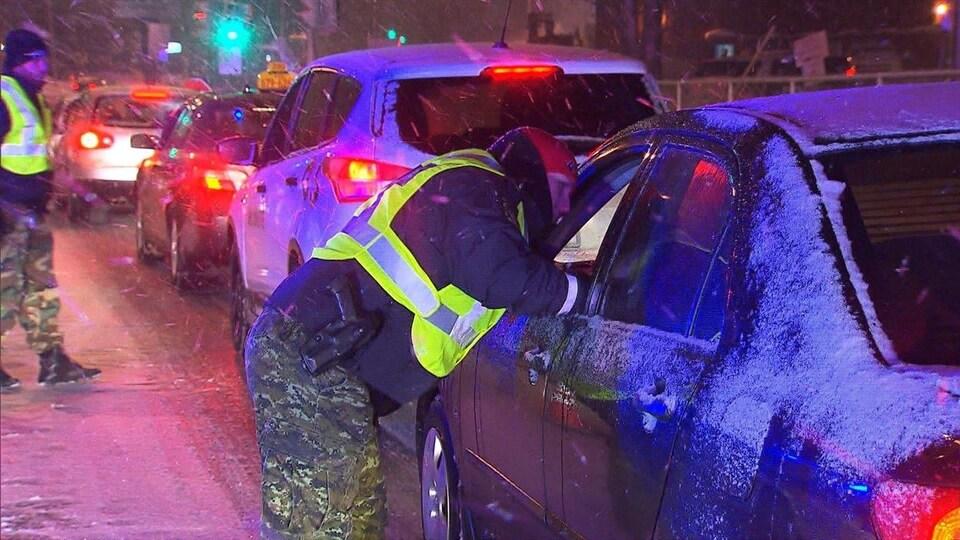 Un patrouilleur aborde un automobiliste immobilisé à un barrage routier