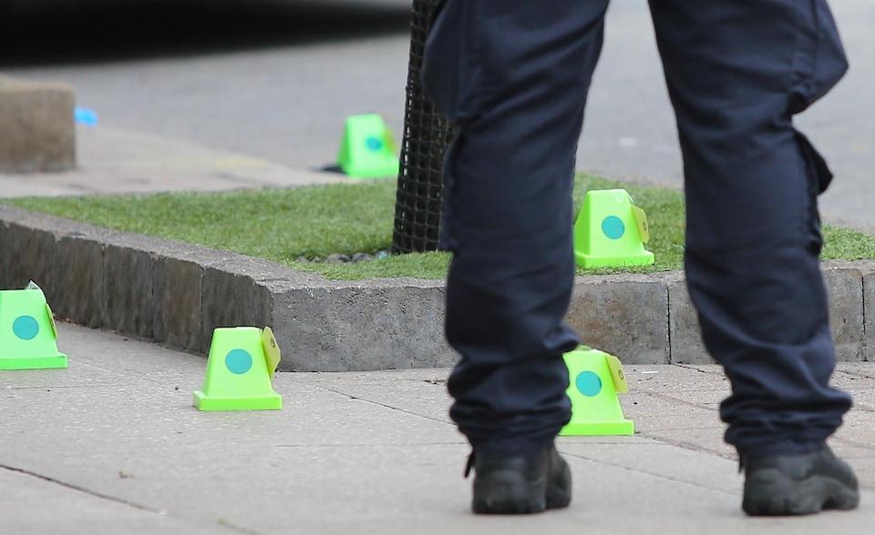 Des jambes d'un policier et des indices identifiés sur une scène de crime.
