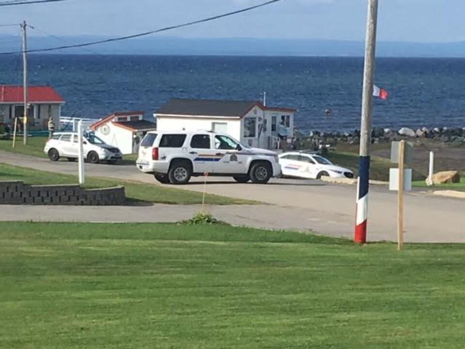 Des voitures de police devant la mer à Grande-Anse.