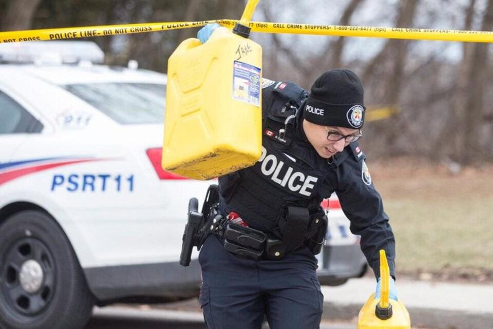 Un agent transporte des conteneurs à l'extérieur d'une maison du la rue Mallory Crescent, à Toronto, où des restes de corps démembrés ont été trouvés.