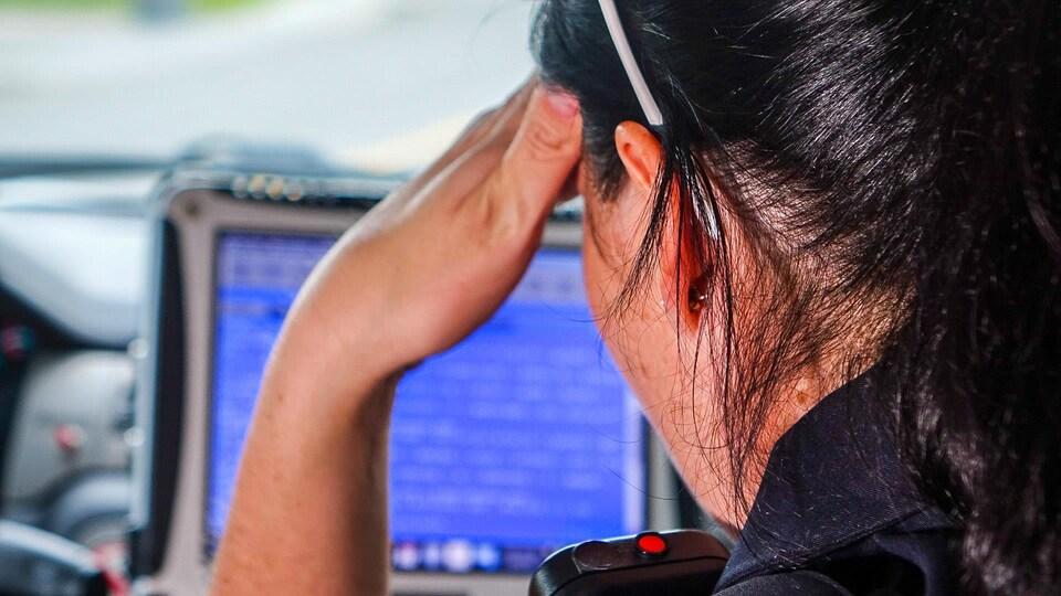 La sergente Julie Marcotte consulte un ordinateur à bord d'une voiture de patrouille du Service de police de la Ville de Québec