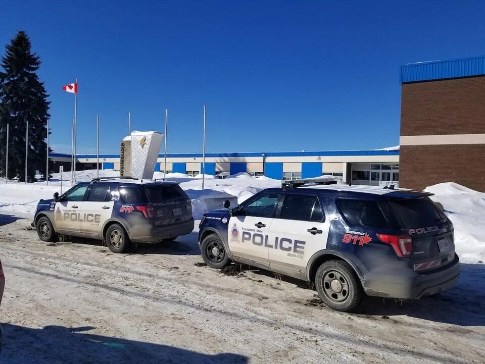 Deux voitures de police devant une école en hiver.