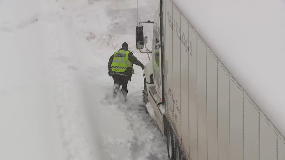 Un policier à côté d'un camion sur l'autoroute 13