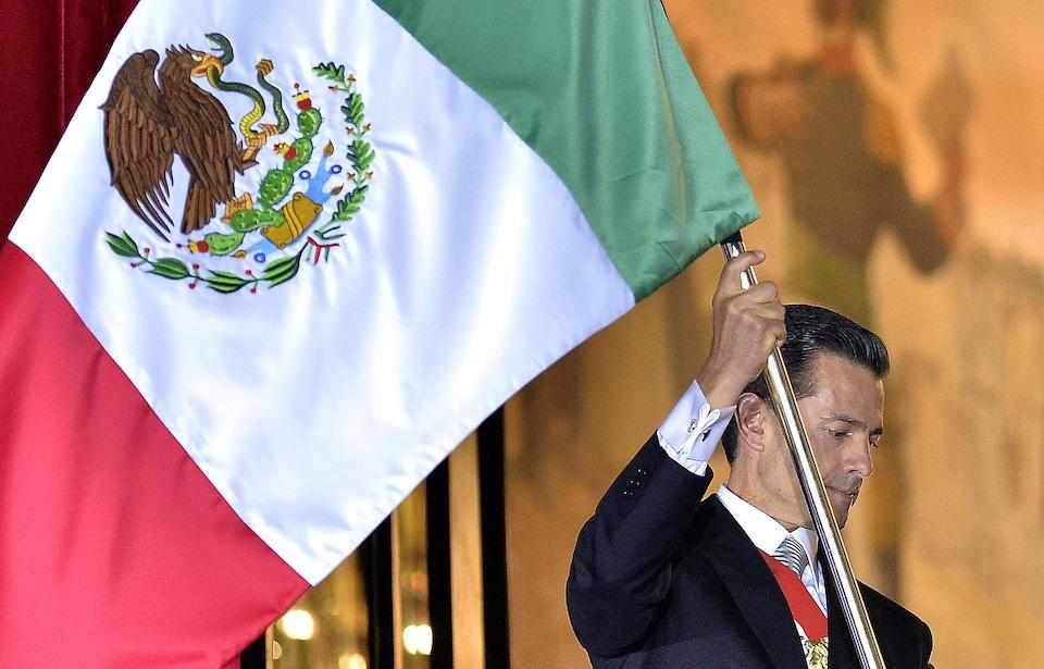 L'ancien président mexicain Enrique Pena Nieto brandit un drapeau du pays du haut d'un balcon du palais national.