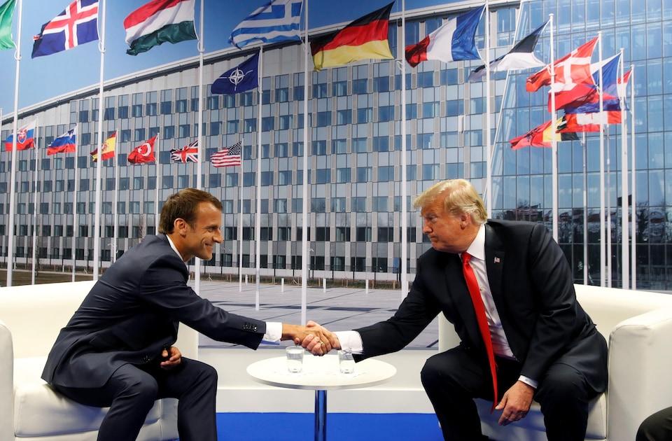 Emmanuel Macron et Donald Trump se serrent la main lors d'une rencontre à Bruxelles.
