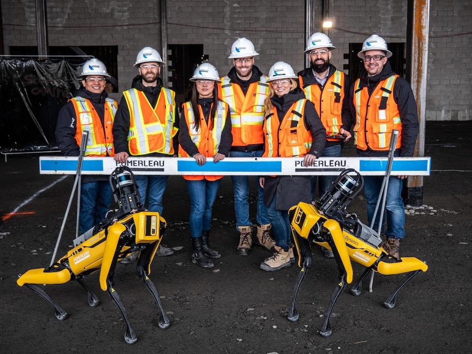 Deux robots Spot devant une équipe de travailleurs et travailleuses de la construction.