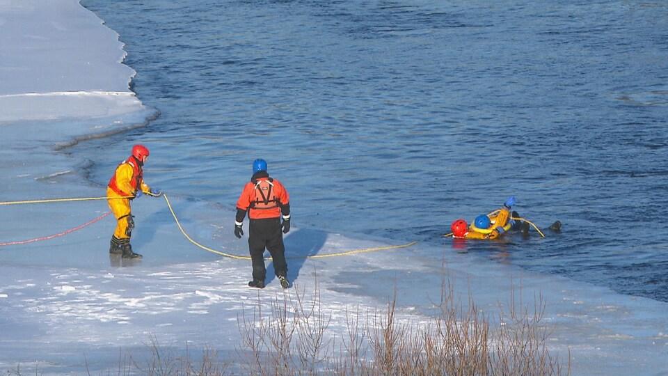 Quatre pompiers en exercice. Deux sont sur la glace, deux sont dans l'eau.