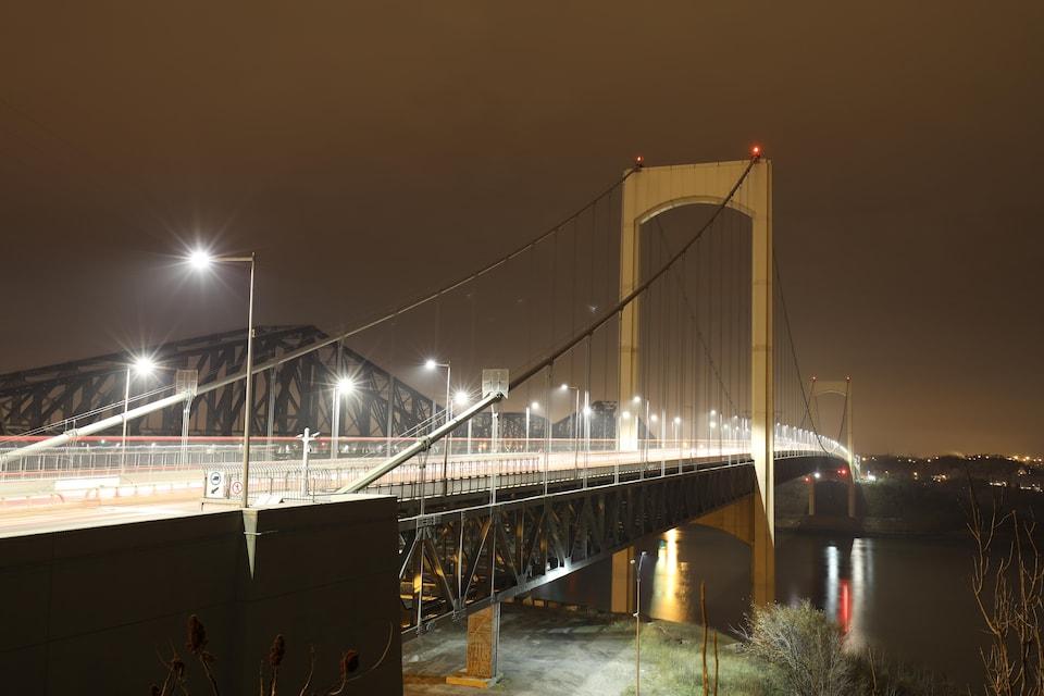 Le pont Pierre-Laporte, vu de la rive nord du fleuve Saint-Laurent, la nuit. Les phares du trafic automobile forment des traits lumineux grâce à l'exposition longue.