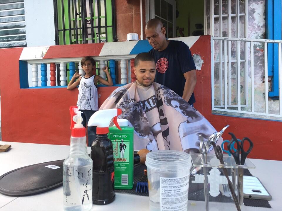 Sans électricité, sans climatisation à Loíza, le barbier Juan Pablo Quiñones, offre ses services à l'extérieur pour la première fois. Dix-sept clients se sont assis dans sa chaise, une très bonne journée pour un lundi, dit-il. Il continuera dehors jusqu'à ce que le courant soit rétabli.