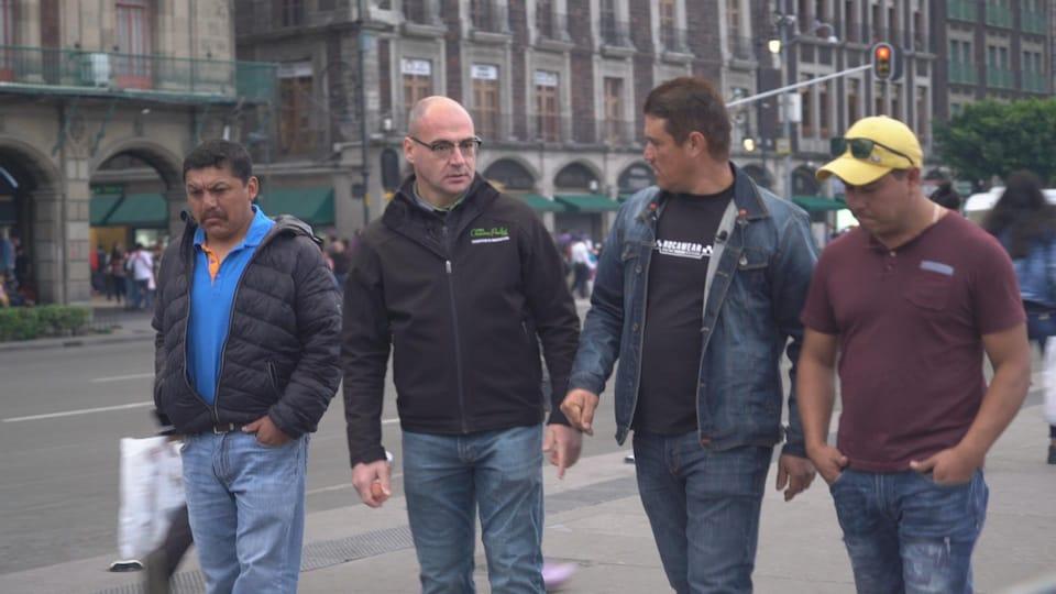 On voit les quatre hommes, de face, en train de marcher au centre de la ville de Mexico.