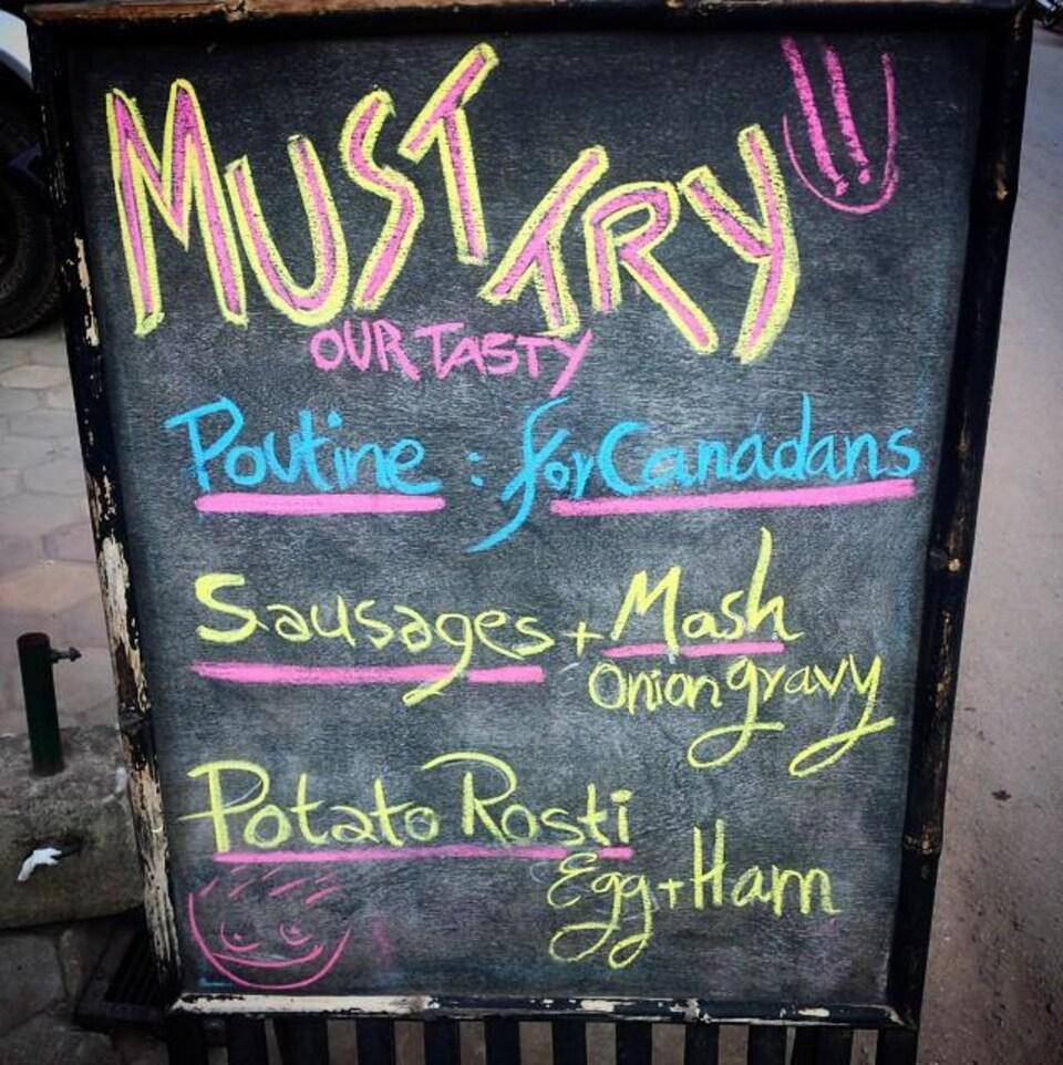 Un panneau en face d'un restaurant à Siem Reap, au Cambodge. Sur le panneau: «Must try our tasty poutine for Canadans»