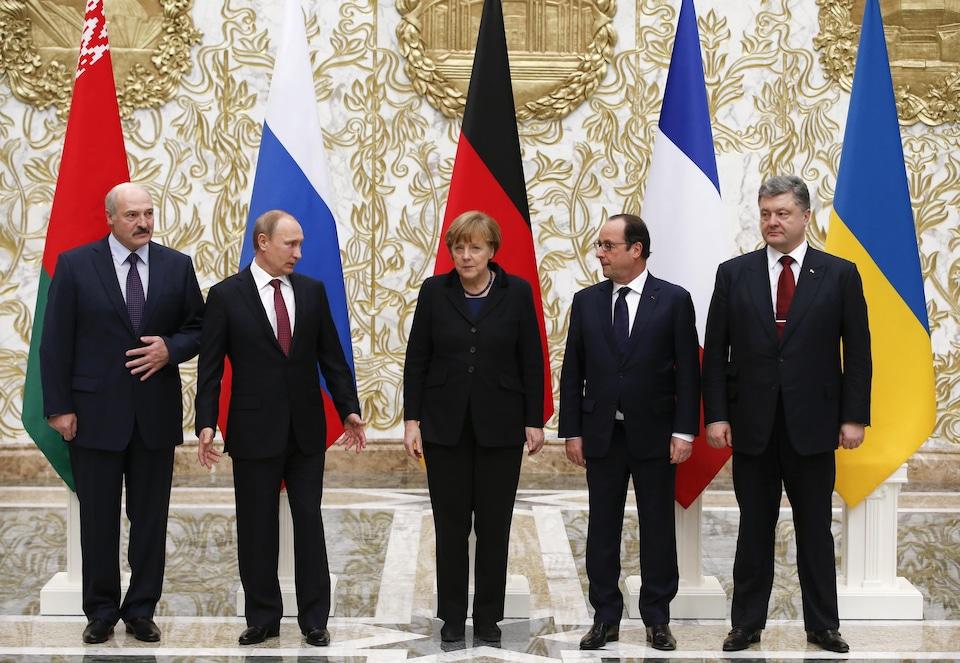 Les politiciens sont en rang devant leurs drapeaux respectifs.