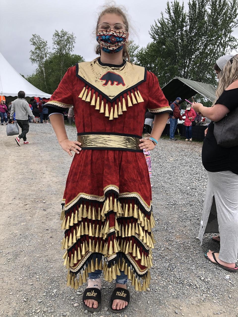 Une jeune femme habillé avec un habit traditionnel autochtone.