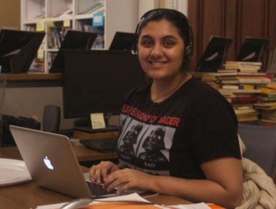 Une jeune indienne assise devant un ordinateur portable
