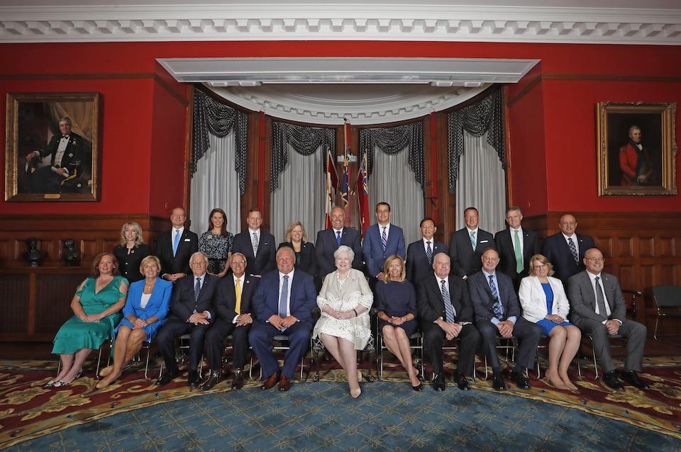 Des hommes et des femmes assis en deux rangées pour une photo de groupe