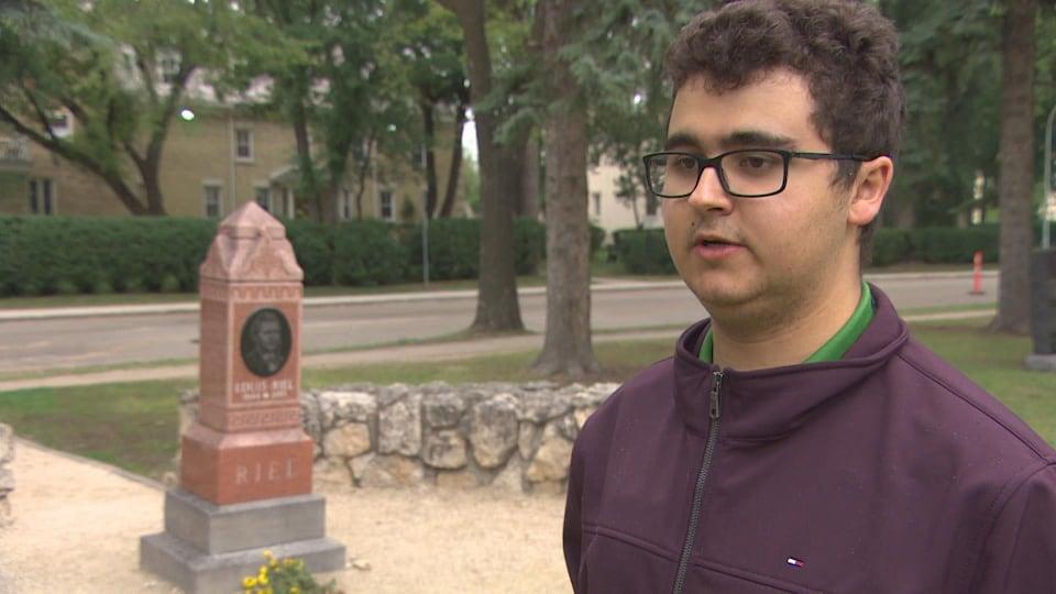 un jeune homme s'adresse à la caméra devant la tombe de Louis Riel.