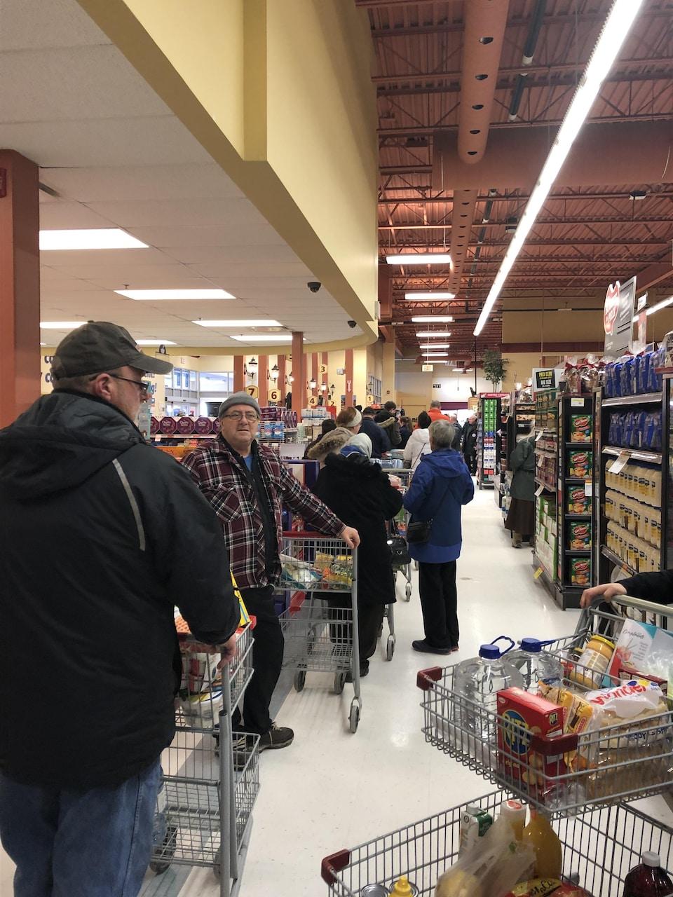 Plusieurs dizaines de personnes attendent à l'épicerie avec un panier plein.